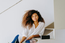 Attractive Young Barefoot Ethnic Female With Long Afro Hairstyle Dressed In Casual White Blouse And Jeans Sitting On Stairs Near Potted Plants And Candle In Modern Apartment