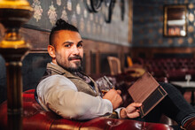 Relaxed Bearded Male Using Tablet And Enjoying Liquor While Resting On Sofa And Looking At Camera In Elegant Pub