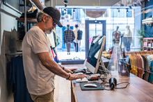 Side View Of Clothing Store Owner Checking Sales On Computer