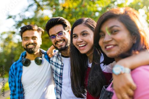 Photo four people having fun outdoors, focus on beautiful indian woman