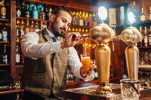 Concentrated Adult Bearded Bartender Tapping Beer Into Glass While Working At Counter In Pub