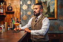 Adult Elegant Man Smelling Liquor Near Tropical Cocktail While Sitting At Counter And Resting In Bar