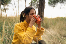 Side View Of Tranquil Female Sitting In Field In Autumn And Drinking Hot Beverage While Enjoying Weekend