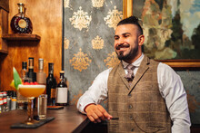 Adult Elegant Man Smiling Looking Away Driking Liquor Near Tropical Cocktail While Sitting At Counter And Resting In Bar