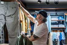 Side View Of Man Choosing Clothes In A Clothing Store