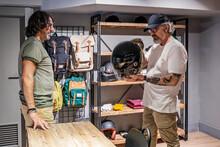 Side View Of Store Owner Advising Customer On Motorcycle Helmets