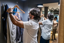 Side View Of Man Trying On Clothes In The Clothing Changing Room Of A Clothing Store