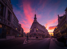 Low Angle Of Metropolis Building On Background Of Colorful Sunset Sky In Madrid In Long Exposure