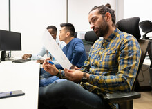 Side View Of Focused Bearded Male Analyst Manager In Casual Outfit Examining Paper With Diagrams While Working In Modern Workspace With Colleagues
