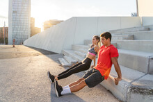 Full Body Side View Of Determined Young Active Man And Woman In Sportswear Doing Reverse Push Ups Against Concrete Steps During Fitness Workout Together On City Street