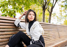 Side View Of Tranquil Dreamy Young Latin Female In Stylish Spotty Outfit Sitting On Wooden Bench And Looking Away Thoughtfully While Resting In Park