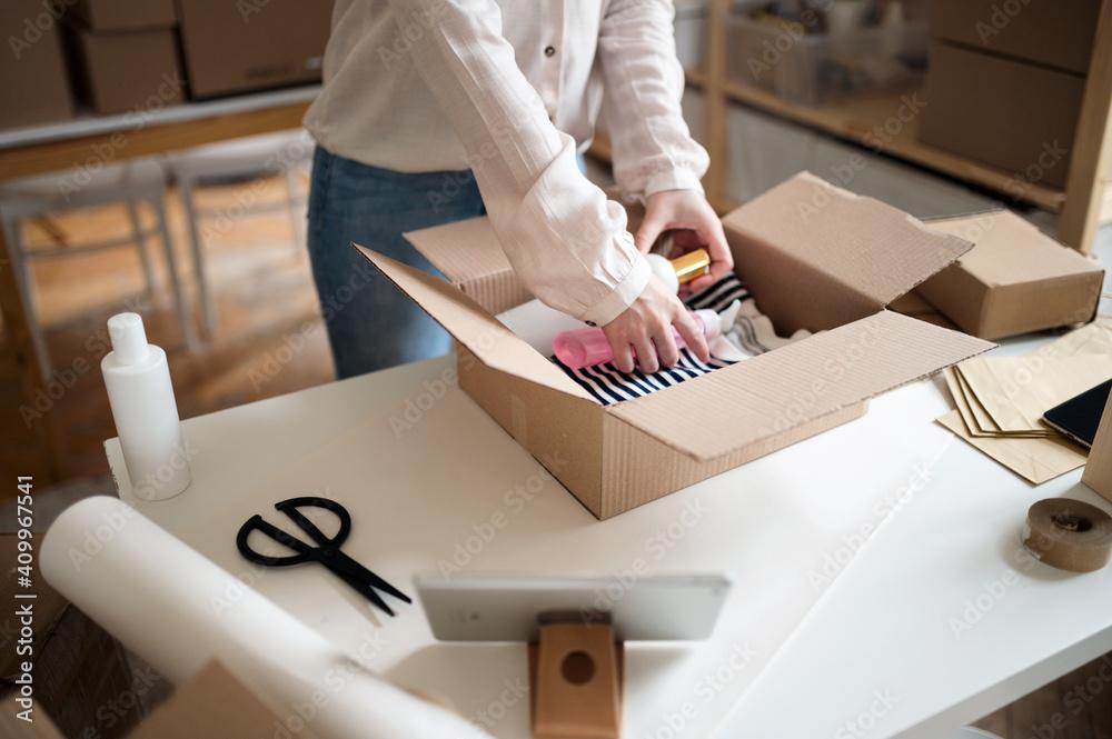 Fototapeta Unrecognizable woman dropshipper working at home, packing parcels. Coronavirus concept.