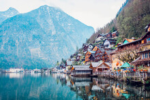 Picturesque Landscape Of Traditional Residential Houses And Famous Lutheran Parish Church Of Hallstatt Located On Lake Shore Surrounded By Mountains In Austria