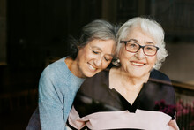 Through Glass View Of Smiling Mature Woman Gently Embracing Elderly Mother Looking At Camera At Home