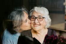 Through Glass View Of Smiling Mature Woman Gently Embracing Elderly Mother And Kissing At Home