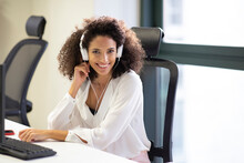 Young Hispanic Female Employee In White Blouse And Headphones Smiling Friendly At Camera While Working At Table With Computer In Modern Workplace