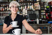Cheerful Female Bartender Standing At Counter With Cup Of Freshly Prepared Coffee And Looking At Camera