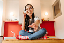 Brown-eyed Woman In Jeans And T-shirt Laughs, Listens To Music On Headphones And Reaches For Camera