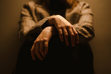 Selective Focus Of Hands Of Crop Anonymous Exhausted Depressive Unhappy Woman In Checkered Coat Sitting In Dark Studio