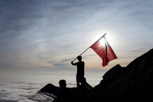 Silhouettes Of Unrecognizable Company Of Hikers Standing With National Taiwan Flag On Yuanzui Mountain During Adventure