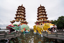 Low Angle Exterior Of Traditional Oriental Pagodas With Colorful Ornamental Tiger And Dragon Sculptures Built On Lake And Connected With Shore By Stone Bridges In Kaohsiung City In Taiwan
