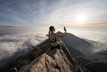 Back View Of Female Ethnic Hiker Sitting On Top Of Yuanzui Mountain And Taking Self Portrait On Smartphone
