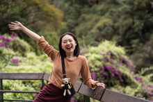 Cheerful Asian Female Tourist Standing On Wooden Terrace With Raised Arm While Enjoying Summer Vacation In Green Park In Hualien City And Looking At Camera