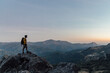 Full body side view of lonely unrecognizable male explorer with backpack standing on top of rough rocky mountain and enjoying freedom while hiking through highlands at sunset