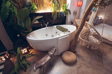 Cozy Hotel Room With White Bathtub And Hanging Rope Chair Near Green Tropical Plants In Traditional Oriental Style In Taiwan