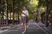 Ethnic Asian Female Using Smartphone And Walking Along Tanya Shen Green Bikeway In Taichung Looking At Camera