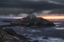 Picturesque View Of Thunderstorm With Flashes Of Lightnings Above Lonely House On Island In Stormy Sea At Sunset