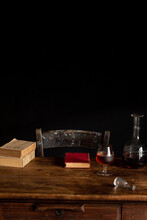 Old Wooden Table With Alcohol Beverage Near Books In Cozy Dark Room With Black Background