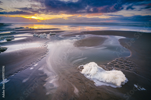 Carta da parati The sunset with the reflection of clouds in low tide water in Waddenzee, Texel,