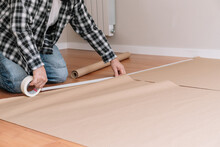 Unrecognizable Male Painter Sticking Craft Paper To Floor With Tape While Preparing Modern Room For Painting And Renovation