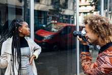 Creative Male Photographer With Camera Shooting Photo Of Stylish Young African American Female Model With Afro Pigtails Near Glass Wall Of Urban Building