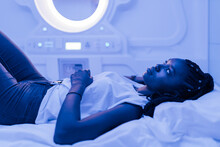 Young Black Woman Resting On Bed In Contemporary Capsule Hotel With Futuristic Interior Design And Blue Illumination Looking Up