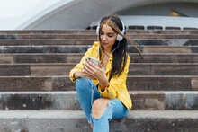Joyful Millennial Woman In Trendy Colorful Outfits And Headphone Sitting On Stone Stairs Browsing Smartphone While Spending Time Together In City