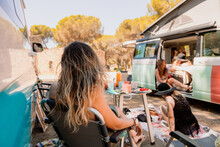 Company Of Female Travelers Relaxing Near Camper Van On Meadow In Woods And Enjoying Summer Trip Together