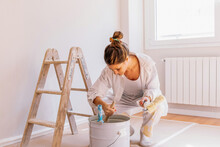 Happy Young Female Taking White Paint With Brush From Bucket While Kneeling On Floor Near Wall During Renovation At Home