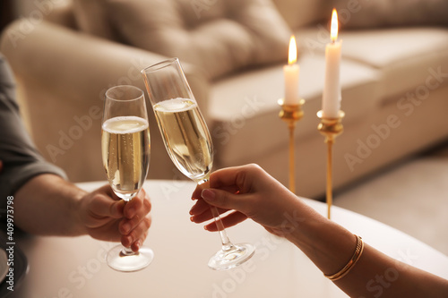 People clinking glasses with champagne at home, closeup Wallpaper Mural