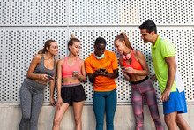 Group Of Multiracial Runners In Activewear Leaning On Wall Of Building And Using Smartphones After Workout In City