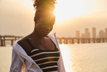 Tranquil Pensive Young African American Female In Casual Clothes Relaxing On Urban Seafront At Sunset Time