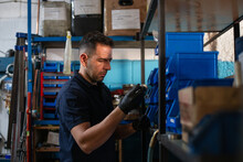 Positive Adult Male Master In Protective Gloves Picking Metal Detail From Box While Choosing Tools For Repair Service In Workshop