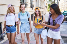 Cheerful Young Multiracial Girlfriends Using Smartphone And Discussing Funny Pictures While Strolling Together On Urban Street In Summer Day