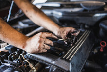 Unrecognizable Technician With Greasy Hands Turning Screw With Spanner While Fixing Engine Of Car In Garage