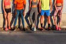 Group Of Crop Unrecognizable Multiethnic Fit Runners In Sportswear Leaning On Wall Of Building While Standing On Street On Sunny Day