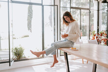 Side View Of Carefree Female Sitting On Table At Home With Glass Of Refreshing Water With Lemon Juice And Enjoying Morning