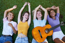 From Above Of Group Of Content Diverse Teen Girlfriends In Casual Outfits With Guitar Chilling Together On Green Grass And Enjoying Summer Holidays In Park