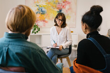 Back View Of Unrecognizable Male In Casual Clothes Wiping Away Tears While Sitting On Chair With Ethnic Wife And Psychologist During Therapy Session