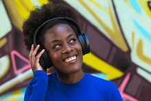 Optimistic Black Female With Afro Hairstyle Listening To Music In Headphones While Standing On Blurred Background Of Graffiti Wall On Street